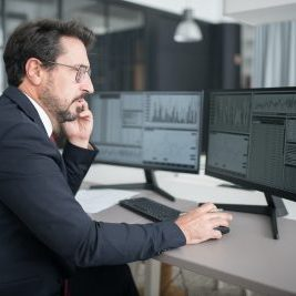 Man at a computer reviewing cash flow charts.